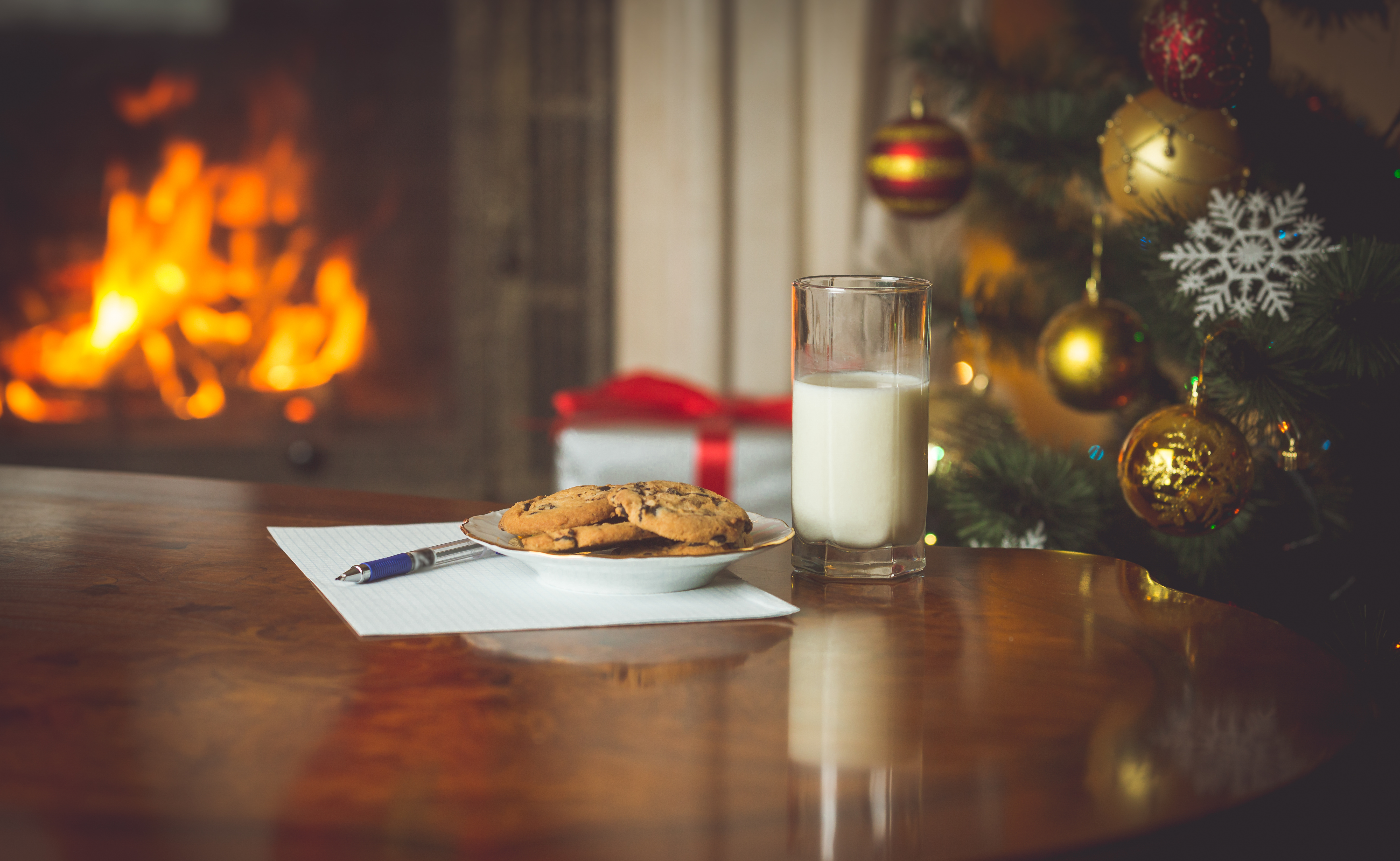 Milk and cookies by a christmas tree