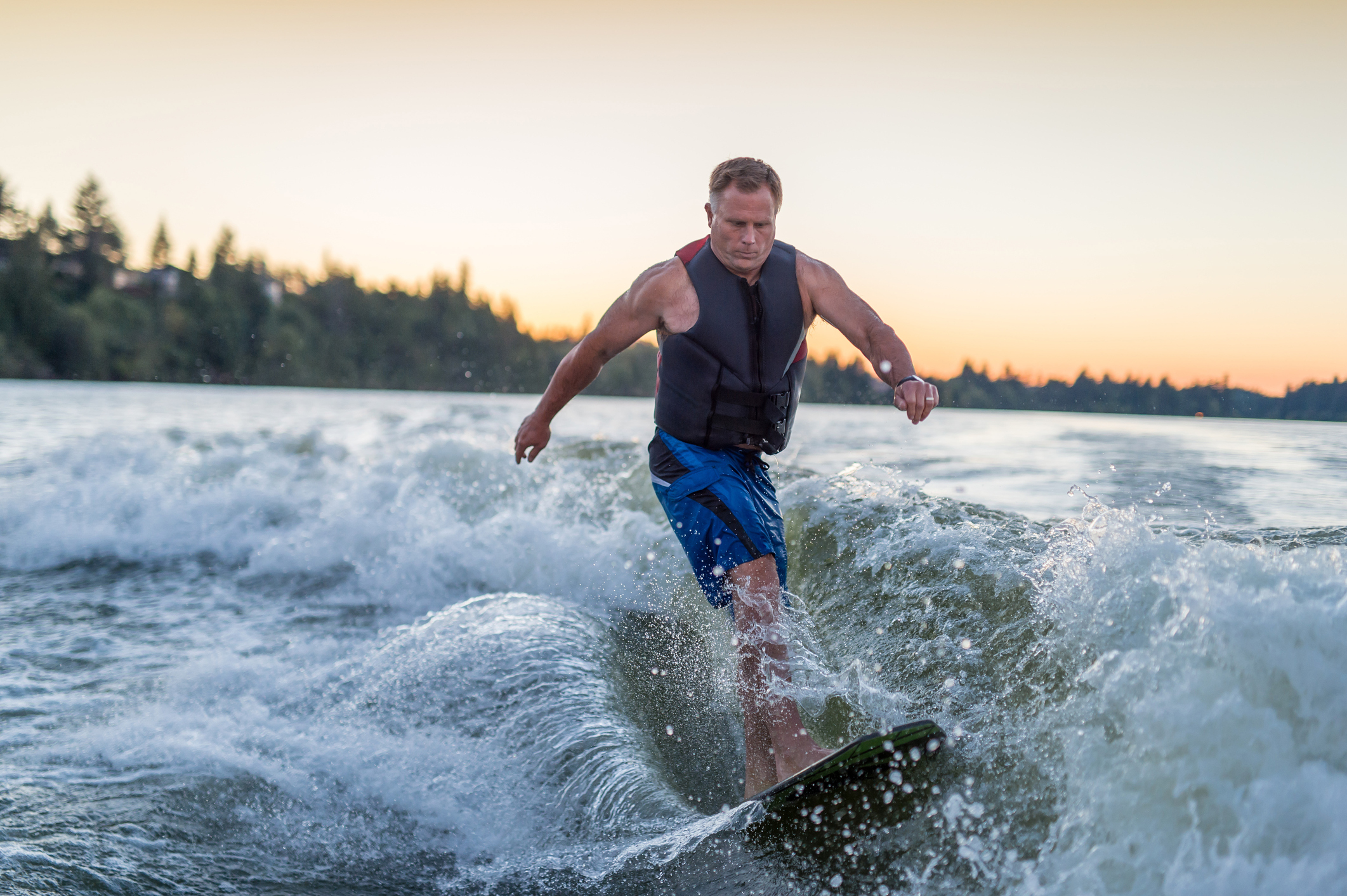 A middle aged man wakeboarding