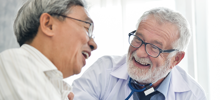 A male doctor and male patient laughing