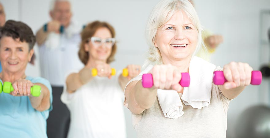 A group of older women working out with dumbells