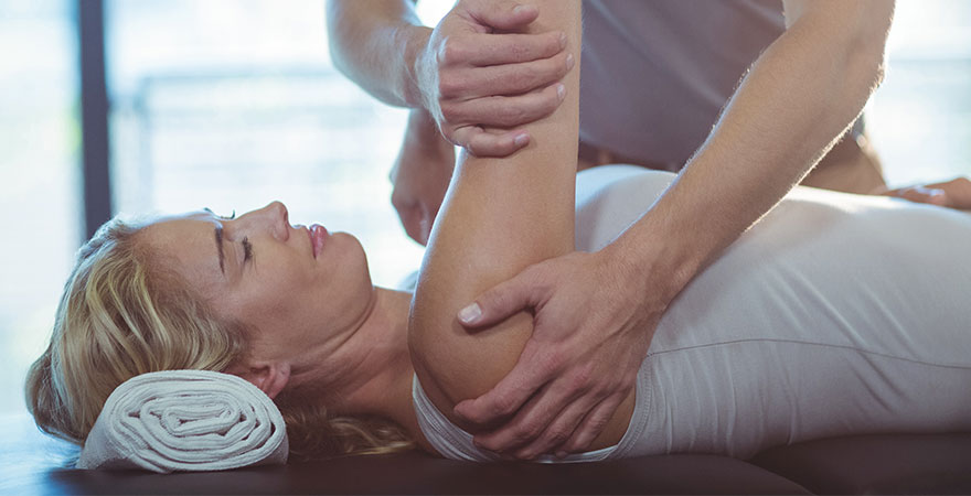 A woman with shoulder pain receiving therapy