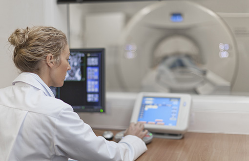 A doctor in front of a CT machine